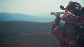 牛仔帽的,皮夹克,蓝色牛仔裤,在他的肩膀的旅游背包一个人 一个人通过望远镜看 股票视频