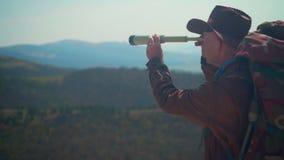 牛仔帽的,皮夹克,蓝色牛仔裤,在他的肩膀的旅游背包一个人 一个人通过望远镜看 股票录像