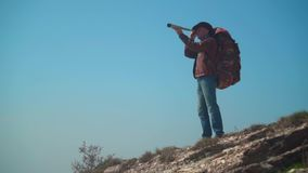 牛仔帽的,皮夹克,蓝色牛仔裤,在他的肩膀的旅游背包一个人 一个人通过望远镜看 影视素材