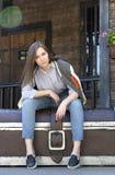 牛仔裤、衬衣和运动衫的女孩坐一大胸口aga 库存照片