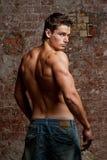 牛仔裤供以人员肌肉赤裸性感的年轻人 免版税库存照片