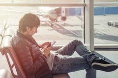 牛仔裤和夹克的年轻人坐椅子花费时间通过使用手机在机场休息室 售票旅馆在外国 免版税库存图片
