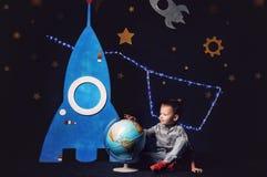 牛仔裤和运动鞋的男孩在玩具火箭和地球旁边坐 图库摄影