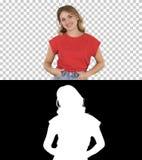 牛仔裤和T恤杉的,阿尔法通道走的妇女 图库摄影