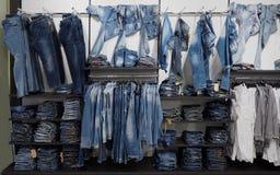 牛仔裤在服装店的架子和衬衣垂悬或安排的牛仔布长裤 免版税库存照片