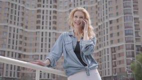 牛仔裤夹克的确信的微笑的白肤金发的妇女谈话由在摩天大楼前面的手机 r 女性城市 影视素材