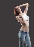 牛仔裤性感的无袖衫脱下衣服妇女年&# 免版税库存图片