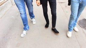 牛仔裤的三个人沿边路走 影视素材