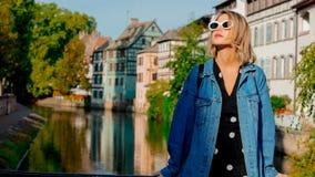 牛仔裤的夹克和太阳镜女孩在史特拉斯堡街道上  免版税库存图片