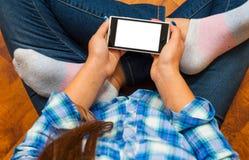 牛仔裤的女孩坐地板和拿着智能手机 少年生活和小配件的概念 库存图片