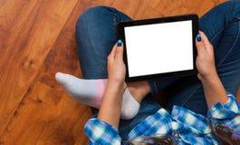 牛仔裤的女孩坐地板和拿着有空白的白色屏幕的一台黑片剂个人计算机 少年生活和小配件的概念 免版税库存照片