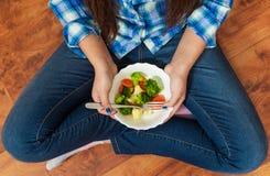 牛仔裤的女孩坐地板并且拿着一块叉子和板材有菜的 空白背景新鲜的庭院混杂的蔬菜 花椰菜、硬花甘蓝和红萝卜 T 免版税库存照片
