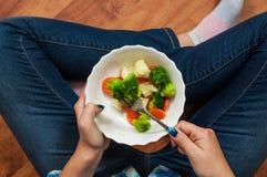 牛仔裤的女孩坐地板并且拿着一块叉子和板材有菜的 空白背景新鲜的庭院混杂的蔬菜 花椰菜、硬花甘蓝和红萝卜 T 库存图片
