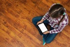 牛仔裤的女孩坐木地板和拿着有空白的白色屏幕的一台黑片剂个人计算机 少年生活和小配件 免版税库存照片