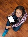 牛仔裤的女孩坐木地板和拿着有空白的白色屏幕的一台黑片剂个人计算机 少年生活和小配件 库存照片