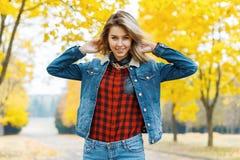 牛仔裤的少妇在秋天公园穿衣 免版税库存照片