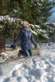 牛仔裤的愉快的女孩在室外绿色的杉树附近跳 免版税库存图片