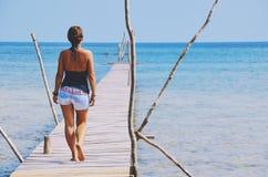 牛仔裤的热的女孩走在码头的由海 库存图片