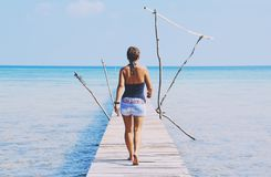 牛仔裤的热的女孩走在码头的由海 库存照片