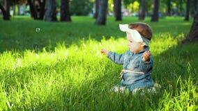 牛仔裤的甜女孩佩带,并且发带坐绿草在晴朗的公园 影视素材