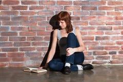 牛仔裤的美丽的年轻红色头发妇女有书的坐地板在砖墙附近 殷勤读有趣 免版税库存照片