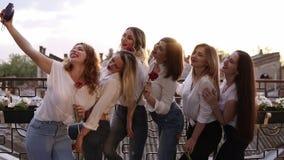 牛仔裤的美丽,魅力妇女和在大阳台的白色衬衣 设法一个的女孩拍所有妇女selfie照片  股票录像