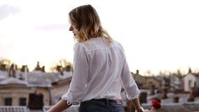 牛仔裤的肉欲,苗条妇女和白色衬衣在有红色花的一个阳台站立在她的手上 白肤金发的女孩 股票录像