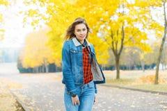 牛仔裤衣裳和一件红色方格的衬衣的俏丽的女孩在秋天 图库摄影