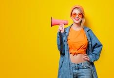 牛仔裤衣裳的女孩有桃红色扩音机的 免版税库存图片