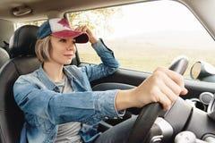 牛仔裤衣裳的微笑对她的汽车轮子的愉快的俏丽的女孩和盖帽  免版税库存图片