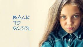 牛仔裤衬衣的美丽的蓝眼睛,白肤金发的少年女孩 在一个轻的背景 回到学校的题字 特写镜头 秀丽和 免版税库存照片