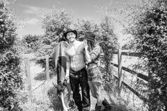 牛仔,女牛仔夫妇男性显示他的六块肌肉吸收 当他们与马和马鞍一起,走两个笑 免版税库存照片