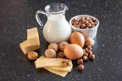 牛奶、乳酪、鸡蛋和坚果在桌上 免版税库存照片
