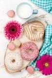 牛奶、油炸圈饼和花在木桌上 库存图片