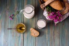 牛奶、蜂蜜和面包在桌上 免版税库存图片