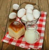 牛奶、鸡蛋和小圆面包 免版税库存照片