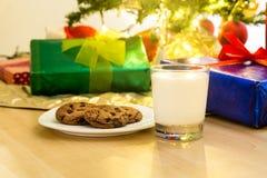 牛奶和曲奇饼圣诞老人的在圣诞树下 免版税库存照片
