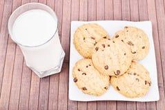 牛奶和曲奇饼在木背景 库存图片