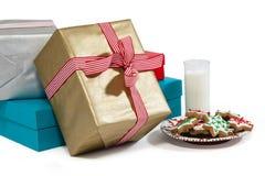 牛奶和甜食物特写镜头在板材有被包裹的礼物的 免版税图库摄影