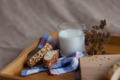 牛奶和面包与干花在木盘子 图库摄影