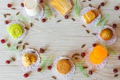 牛奶在面包蒜味面包香蕉杯形蛋糕橙汁过去杯形蛋糕曲奇饼蛋糕卷向日葵种子和鹅莓涂黄油在白色木 库存图片
