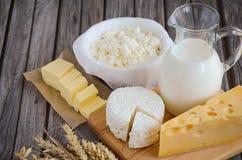 牛奶店新鲜的产品 牛奶、乳酪、黄油和酸奶干酪用麦子在土气木背景 免版税图库摄影
