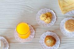牛奶橙汁过去曲奇饼香蕉杯形蛋糕杯形蛋糕和黄油面包在白色木表上 库存图片