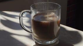 牛奶涌入一个杯子热的咖啡 影视素材