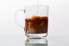 牛奶涌入了一个透明杯子无奶咖啡 免版税图库摄影