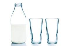 牛奶瓶和两块空的玻璃 免版税库存照片