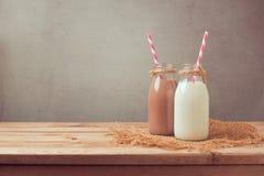 牛奶瓶和巧克力牛奶瓶在木桌上 吃健康 免版税库存图片