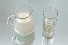 牛奶罐和一块空的玻璃 图库摄影