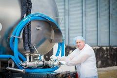 牛奶运输司机与司机的 免版税库存照片