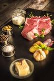 牛排、新鲜的肉oo石头板材、美食术、大蒜和葱,香料,迷迭香用肉,黄油,木桌,添加剂, preparat 免版税库存图片